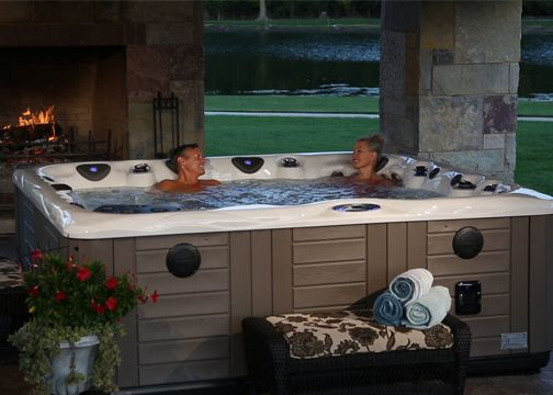 A couple talking in a hot tub with fireplace and lake in the background.